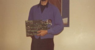 Bill Fernandez holds an Apple I, with an Apple II on the desk.  Photo courtesy of Bill Fernandez